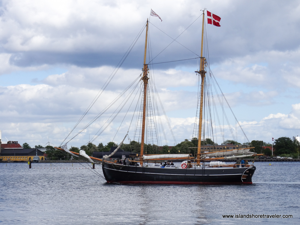 Double-masted schooner with Danish flag heads out to sea for a sail